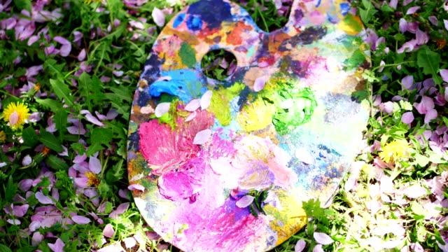 vídeos de stock, filmes e b-roll de close-up, na grama verde encontra-se uma paleta de madeira com tintas coloridas. de cima, caem as pétalas de cerejeira rosa - arte e artesanato assunto