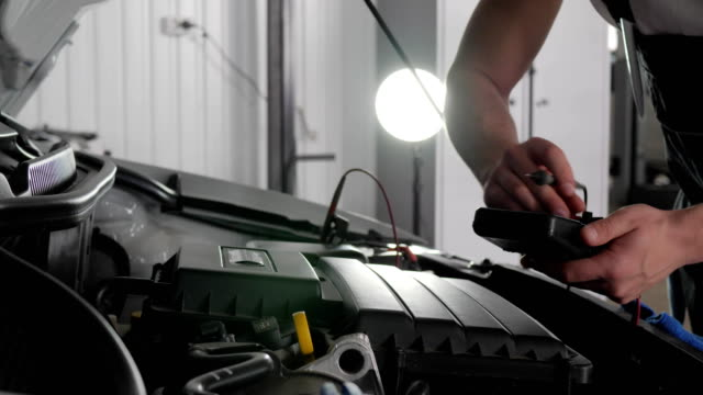 Close-up, open hood, mechanic's hands, in car workshop, check electrical wiring vehicle system, review engine and all automobile parts video
