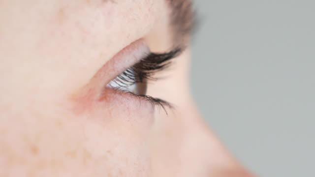 クローズアップオープンブラウン女性の目.光から細める - まつげ点の映像素材/bロール