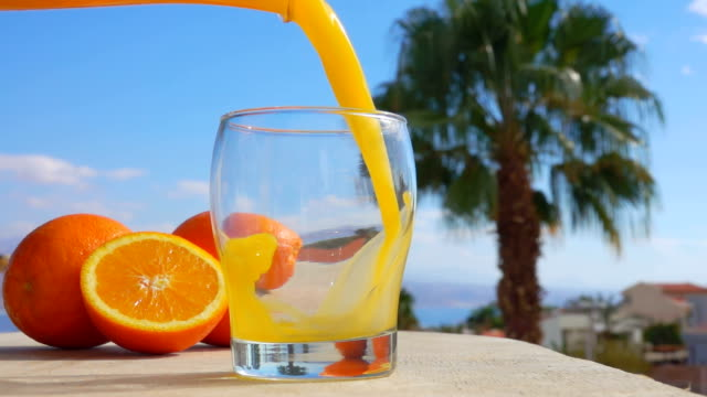 Close-up orange juice poured into a glass Orange juice is poured into a glass against the background of the sunny sea landscape, close-up camera motion orange juice stock videos & royalty-free footage