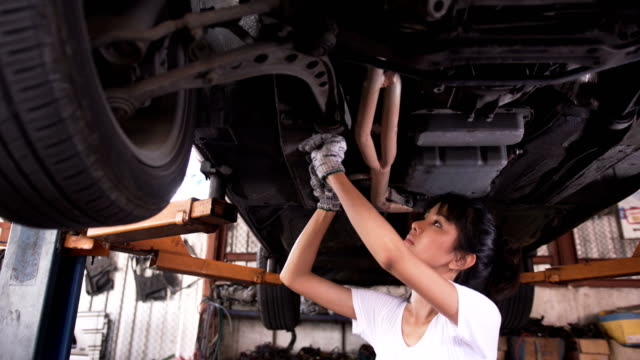 close-up panning low angle view: Young woman mechanic fixing by using wrench under car video