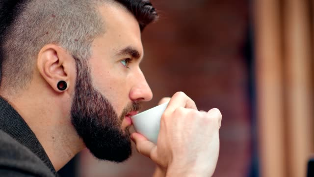 Close-up pensive hipster attractive male with beard thinking drinking fragrance coffee holding cup
