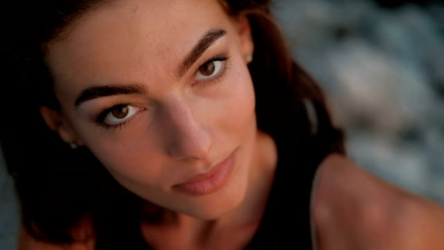 close-up portrait from top to bottom of passionate brunette woman who stares and smiles - красавица стоковые видео и кадры b-roll