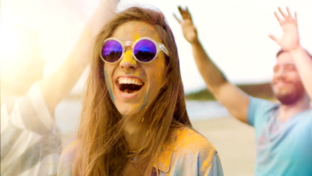 close-up portrait of a beautiful blonde girl dances in celebration of holi festival with her friends. her face and clothes are covered with colorful powder. people dancing in the background. - hippy video stock e b–roll