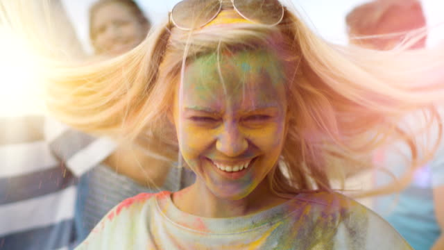 vídeos de stock e filmes b-roll de close-up portrait of a beautiful blonde girl dances in celebration of holi festival with her friends. her face and clothes are covered with colorful powder. - holi