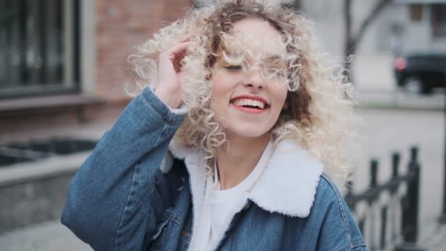 stockvideo's en b-roll-footage met close-up portret van een vrolijke mooie en zorgeloze meisje lopen rond de stad. - blond curly hair