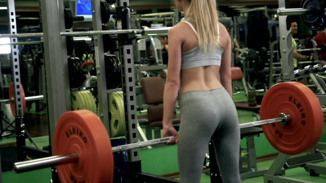 Close-up portrait of a fitness young girl doing squats with barbell at the gym isolated on a black background video
