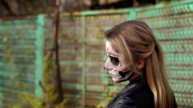 Close-up portrait of a gothic girl in a dress and a creepy make-up. Halloween. Close-up portrait of a gothic girl in a wedding dress and a creepy make-up. Painted skull on the girl's face. Gothic look. Outfit for halloween. Slow motion. skull stock videos & royalty-free footage