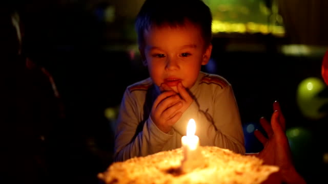 Close-up portrait of a little boy blows out the candles on the cake video
