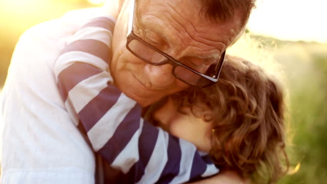 closeup portrait of a mature man hugging his late son. happy fatherhood. curly child, a man wearing optical glasses. colorful sunset - grandparents stock videos & royalty-free footage