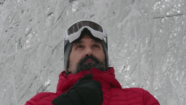 close-up portrait of a mature man putting his ski googles on in the snow at a ski resort. enjoying the winter mountain. preparing for skiing in the snow white mountains. downhill skiing. - occhiali protettivi video stock e b–roll