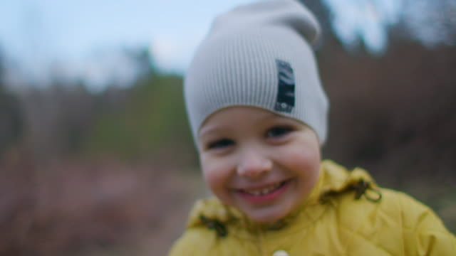 close-up portrait of a small beautiful smiling boy with big eyelashes in a cap and yellow jacket looking directly at the camera. - 2 3 anni video stock e b–roll