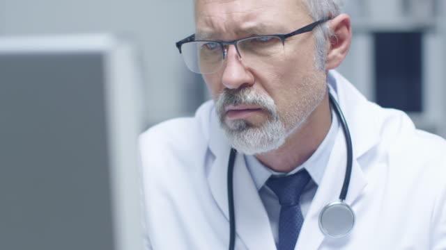 Close-up Portrait von weißen Haaren Arzt arbeitet auf Personal Computer. Sein Büro ist hell und Licht. – Video