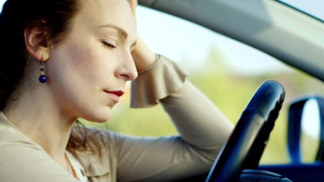 Close-up portrait of a woman, sad. A sad face in the car. Concept - depression, women's problems video