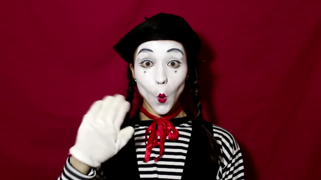 close-up portrait of a young mime girl. beautiful mime girl smiles and waves her hand in greeting. girl in the image of a mime waves her hand when welcoming clients. - гримировальные краски стоковые видео и кадры b-roll