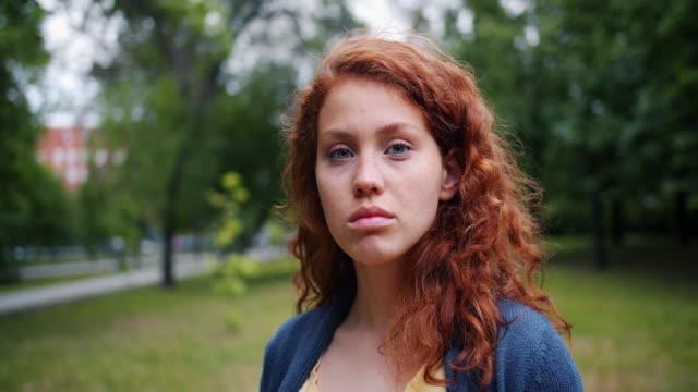 zbliżenie portret uroczej młodej kobiety w parku z poważną twarzą, a następnie uśmiechnięty - surowy obraz filmowy filmów i materiałów b-roll