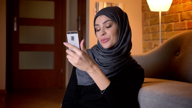Closeup portrait of adult attractive muslim female in hijab having a video call on the phone while sitting on the floor in doorway in a cozy apartment