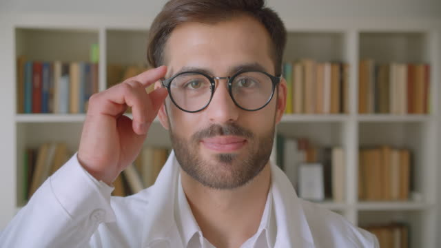 nahaufnahme porträt von erwachsenen stattlichen kaukasischen geschäftsmann in brille blick auf die kamera in der bibliothek mit bücherregalen auf dem hintergrund drinnen - brille stock-videos und b-roll-filmmaterial