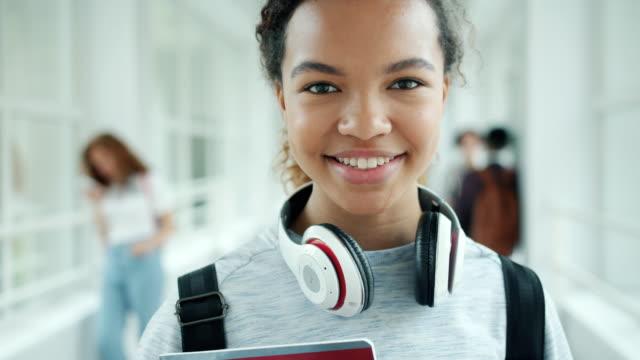 üniversite salonunda gülümseyen afro-amerikan bayan öğrencinin yakın çekim portresi - sırt çantası stok videoları ve detay görüntü çekimi