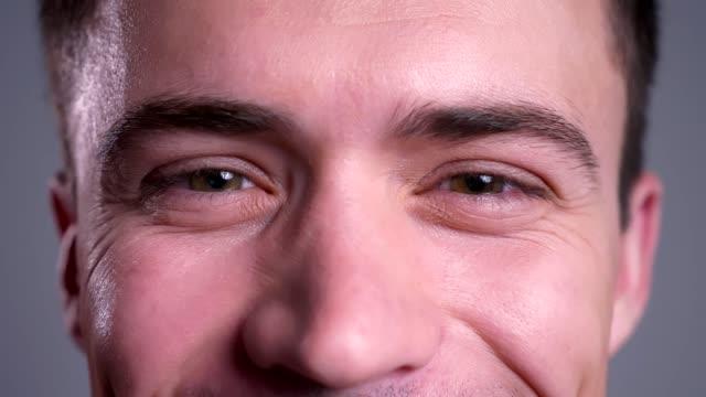 портрет крупным планом привлекательных кавказских мужских карих глаз, смотря прямо в камеру с улыбающимся выражением лица - близко к стоковые видео и кадры b-roll