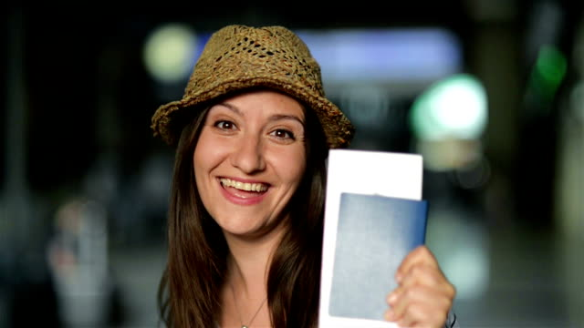 Closeup Portrait of Attractive Smiling Brunette in Summer Hat Waiting for Her Airplane at the Airport with Ticket and Passport in the Hands Closeup Portrait of Attractive Smiling Brunette in Summer Hat Waiting for Her Airplane at the Airport with Ticket and Passport in the Hands, HD. passport stock videos & royalty-free footage