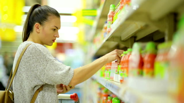 Closeup Portrait of Attractive Young Girl Choosing Juice in the Supermarket Standing Near Shelf