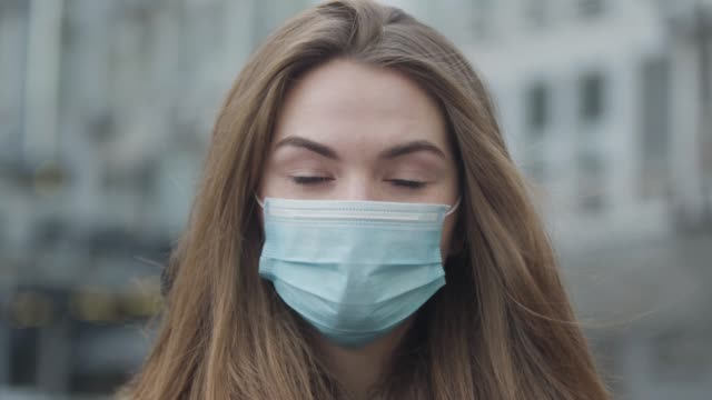 Close-up portrait of beautiful brunette woman with green eyes standing on city street wearing protective mask. Coronavirus hazard, protection, healthcare.