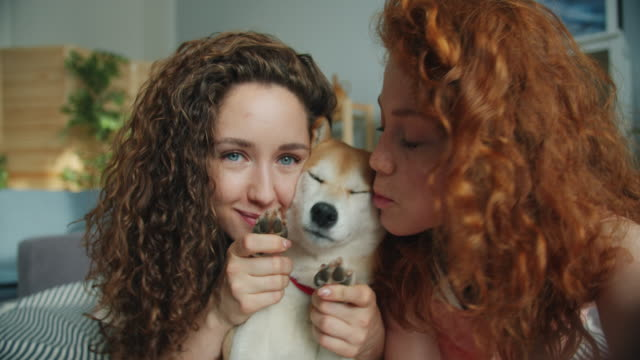 Close-up portrait of beautiful girls and dog taking selfie at home lying on bed