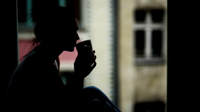 closeup portrait of beautiful woman vor dem fenster mit tasse heißes getränk am morgen. silhouette der erstaunliche mädchen, genießen kaffee allein sitzt auf der fensterbank - introspektion stock-videos und b-roll-filmmaterial