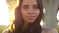 istock Close-up portrait of beautiful young adult woman in the sunlight at sunset. Pretty girl is smiling. She is cute and funny. Beautiful woman is enjoying warm and sunlight. She is basking in the sun 1278608562