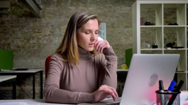 nahaufnahme porträt von konzentrierten büromitarbeiterinnen, die auf den laptop tippen und schwierigkeiten haben und eine lösung für das problem finden - introspektion stock-videos und b-roll-filmmaterial