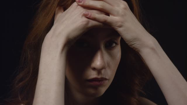 Closeup portrait of depressed young caucasian female looking at camera and on the sides being close to start crying Closeup portrait of depressed young caucasian female looking at camera and on the sides being close to start crying redhead stock videos & royalty-free footage