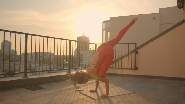 closeup portrait of flexible female with dreadlocks practicing yoga asanas on rooftop in city with beautiful sunrise on background - balcone video stock e b–roll