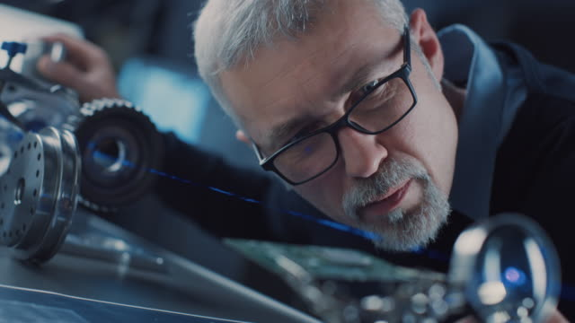 close-up portrait of focused middle aged engineer in glasses working with high precision laser equipment, using lenses and optics for accuracy electronics. - quality video stock e b–roll