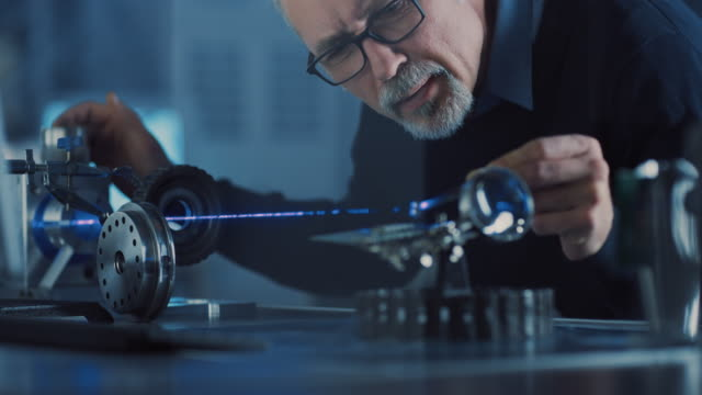 close-up portrait of focused middle aged engineer in glasses working with high precision laser equipment, using lenses and testing optics for accuracy required electronics - dokładność filmów i materiałów b-roll