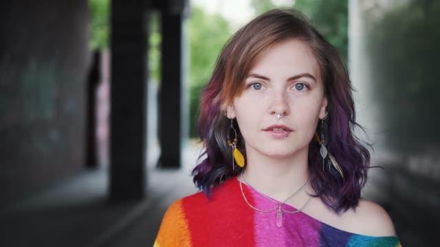 närbild porträtt av flicka med färgat hår och ansikts piercing. ung kvinna med fräknar tittar in i kameran och ler. - rött hår bildbanksvideor och videomaterial från bakom kulisserna