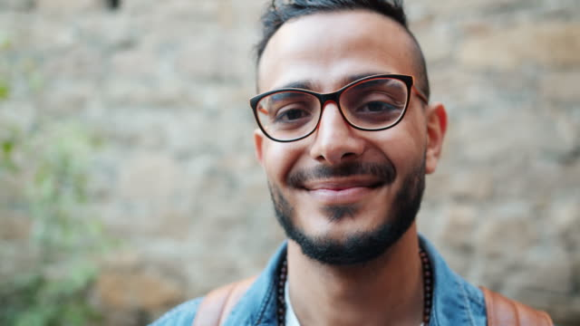 close-up portrait of good-looking arabian man in glasses standing outdoors - baffo peluria del viso video stock e b–roll