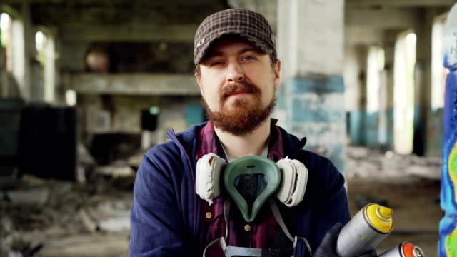 närbild porträtt av stilig skäggig man graffitikonstnär står inne i övergivna byggnaden bär mössa, handskar och pespirator och håller sprayfärg - väggmålning bildbanksvideor och videomaterial från bakom kulisserna