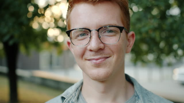 stockvideo's en b-roll-footage met close-up portret van knappe redhead man met sproeten glimlachend buitenshuis - roodhoofd