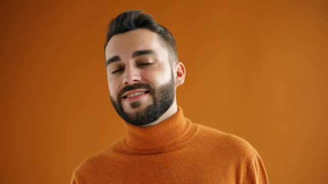 close-up portrait of handsome young bearded man winking looking at camera - solo un uomo giovane video stock e b–roll