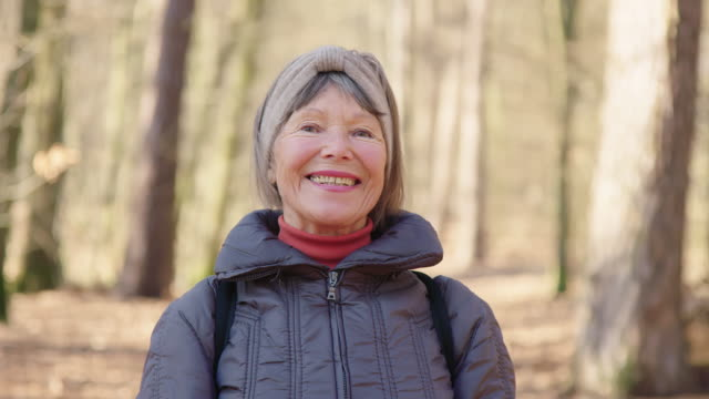 Close-up portrait of happy senior woman in forest