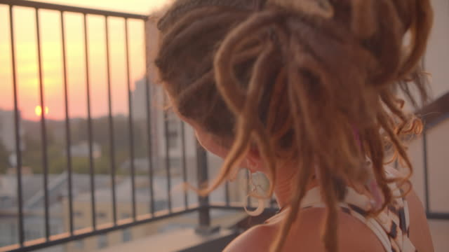 Closeup portrait of hipster caucasian female with dreadlocks meditating and stretching on rooftop with beautiful sunset on background Closeup portrait of hipster caucasian female with dreadlocks meditating and stretching on rooftop with beautiful sunset on background. locs hairstyle stock videos & royalty-free footage