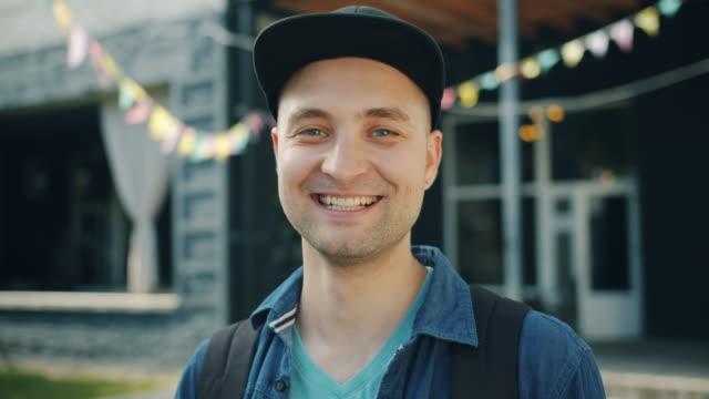 vídeos de stock, filmes e b-roll de retrato do close-up do riso alegre do estudante que sorri ao ar livre na rua da cidade - boné