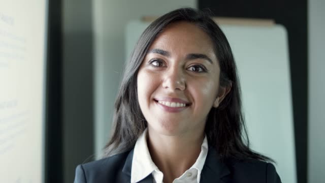 Closeup portrait of Latin beautiful young businesswoman Closeup portrait of Latin beautiful young businesswoman standing in office room. Confident brunette secretary in suit smiling and looking at camera. Human resources, personnel and business concept contented emotion stock videos & royalty-free footage