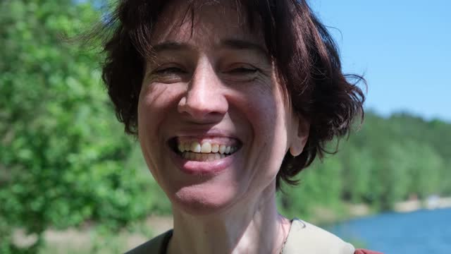 Close-up portrait of  laughing mature woman walking in nature park video