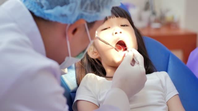 vídeos y material grabado en eventos de stock de retrato de cerca de la niña abriendo la boca de par en par durante la inspección de la cavidad oral por el dentista. linda niña sentada en la silla dental y teniendo tratamiento dental. chequeo dental, tecnología, concepto de personas. - ortodoncista