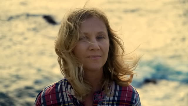 close-up portrait of mature blonde woman who loves adventure travel on the background of the sea waves and wind Strongest close-up portrait of a mature blonde woman who loves adventure travel on a background of sea waves and the windy wind 50 54 years stock videos & royalty-free footage