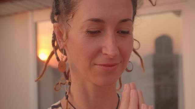 vídeos de stock, filmes e b-roll de retrato do close up da fêmea consciente com dreadlocks que praticam a ioga que sorri feliz no telhado com a paisagem bonita da cidade no fundo - característica arquitetônica