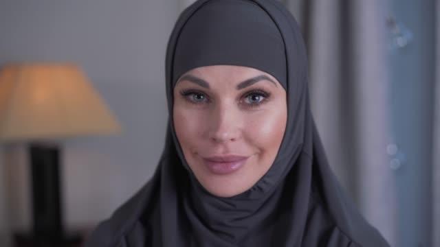 närbild porträtt av modern utseende kvinna med grå ögon i hijab. ung självsäker dam tittar på kameran och ler. livsstil, kultur, skönhet. - anständig klädsel bildbanksvideor och videomaterial från bakom kulisserna