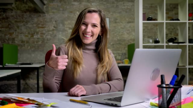 Closeup portrait of pretty female office worker sitting in front of the laptop smiling and showing thumb up